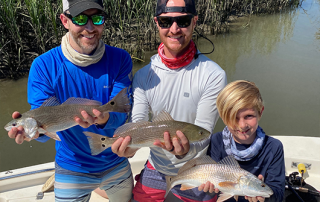 family holding 3 fishes